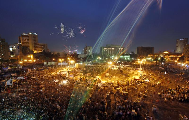 Fireworks streak across the sky as protesters fill Tahrir Square in Cairo, Egypt, Friday, April 20, 2012. Tens of thousands of protesters packed Cairo's downtown Tahrir Square on Friday in the biggest demonstration in months against the ruling military, aimed at stepping up pressure on the generals to hand over power to civilians and bar ex-regime members from running in upcoming presidential elections. (AP Photo/Khalil Hamra)