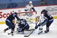 Winnipeg Jets' Nathan Beaulieu (88) clears the puck in front of goaltender Connor Hellebuyck (37) as Vancouver Canucks' Elias Pettersson (40) looks for the rebound during second period NHL hockey action in Winnipeg, Manitoba on Tuesday March 1, 2021. (Fred Greenslade/The Canadian Press via AP)