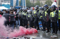 People run away as a smoke flare is set off in front of a police line near Leicester Square in London, Sunday, July 11, 2021, during the Euro 2020 soccer championship final match between England and Italy which is being played at Wembley Stadium. (AP Photo/Peter Morrison)