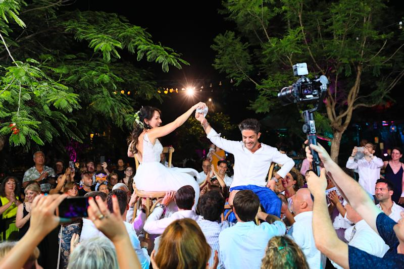 The couple sit on chairs and are lifted into the air. [Photo: Denis Butnaru Photography]
