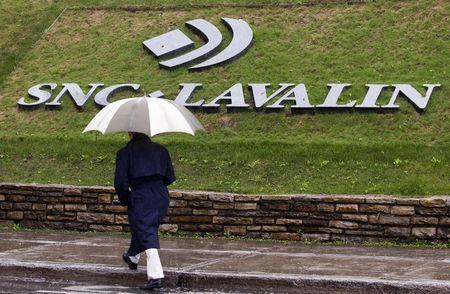A pedestrian walks past the SNC-Lavalin Group Inc., headquarters in Montreal