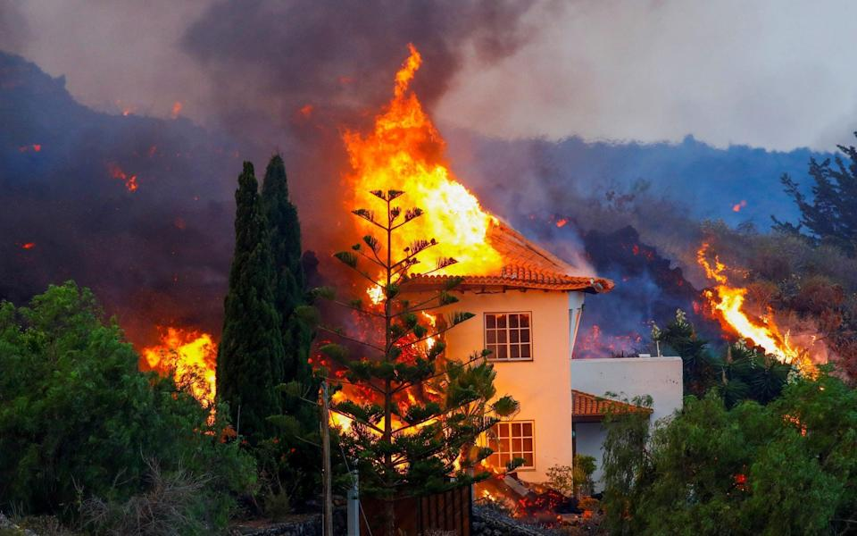 A house burns due to lava from the eruption of a volcano - Borja Suarez/REUTERS