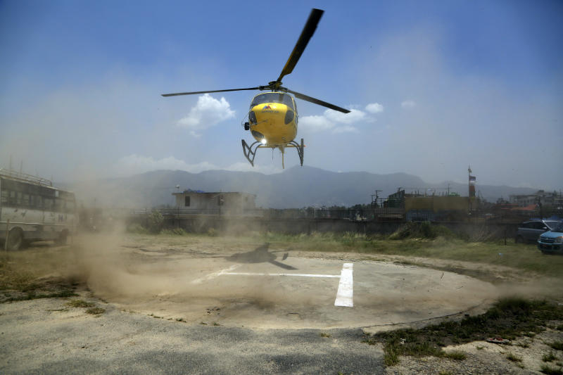 A helicopter carrying dead bodies of two Indian mountaineers arrives at Teaching hospital in Kathmandu, Nepal, Sunday, May 19, 2019. Two mountaineers died on Nepal's famous Himalayan peaks, while another two climbers were missing, officials said Friday. (AP Photo/Niranjan Shrestha)
