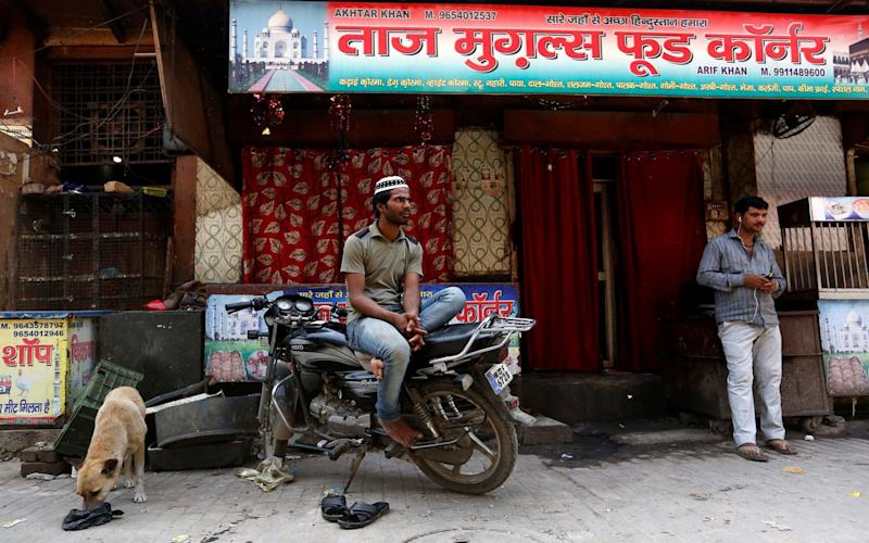 A Muslim man looks on outside a closed restaurant in Gurugram - REUTERS