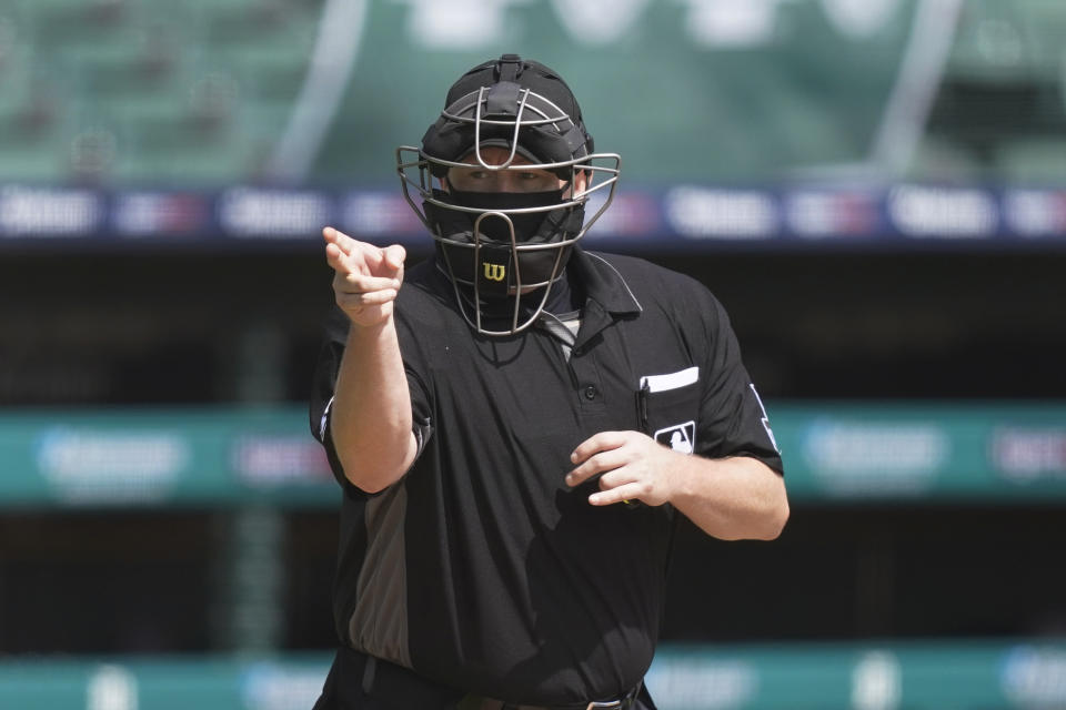 Home plate umpire Todd Tichenor signals during the fourth inning of the first baseball game of a doubleheader between the Detroit Tigers and the Minnesota Twins, Saturday, Aug. 29, 2020, in Detroit. (AP Photo/Carlos Osorio)
