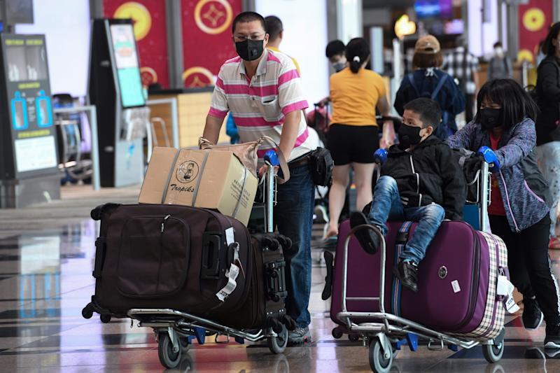 Travellers wear protective facemasks at the departure hall of Changi Airport on 30 January, 2020. (PHOTO: AFP via Getty Images)