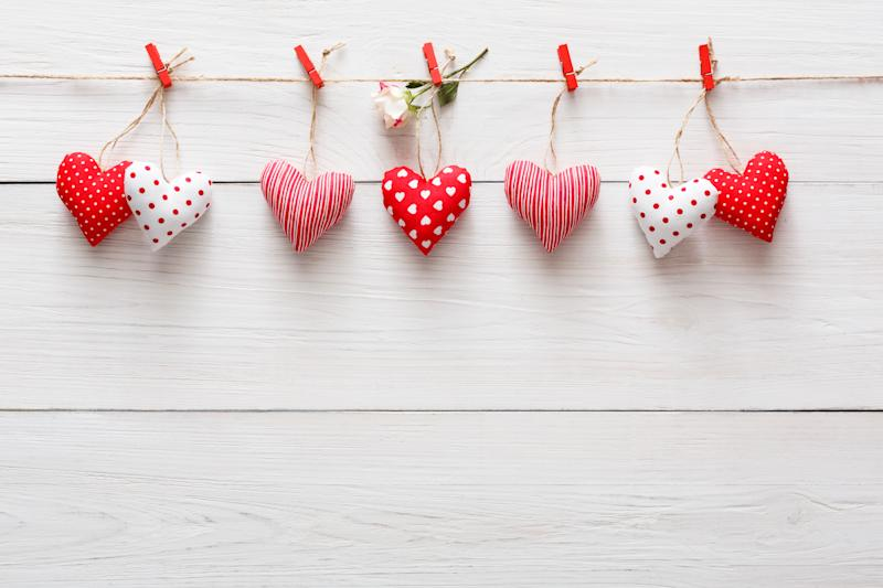 Valentine background with diy sewed pillow hearts row border on red clothespins at rustic white wood planks. Happy lovers day card mockup, copy space