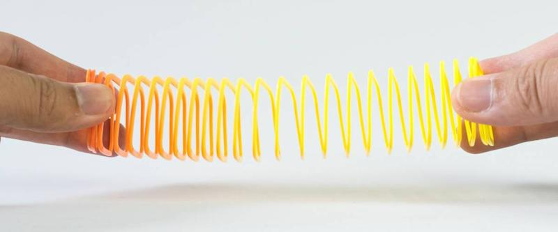 Hand holding elastic spring coil on empty background. Concept of business flexibility. Slightly de-focused and close-up shot. Copy space.