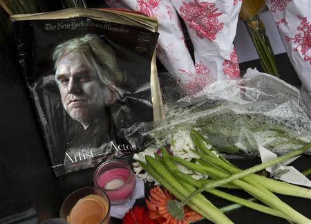 A copy of a New York Times Magazine with a photo of movie actor Philip Seymour Hoffman on the cover is pictured as part of a makeshift memorial in front of his apartment building in New York February 3, 2014. REUTERS/Carlo Allegri
