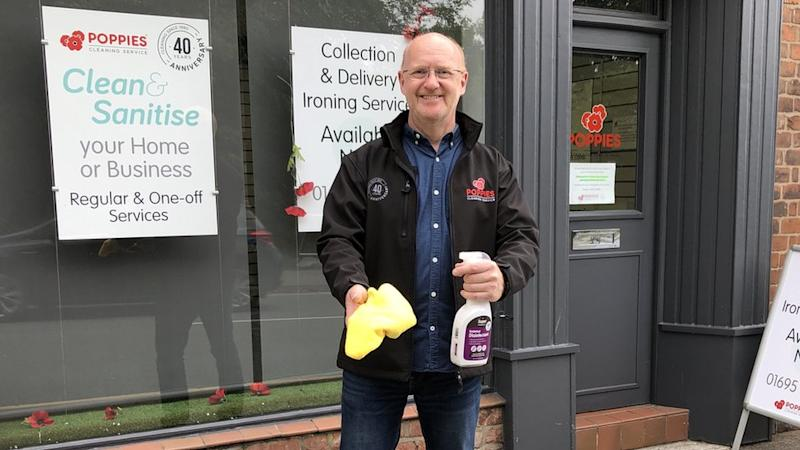 The boss of cleaning firm Poppies, Chris Wootton holding a spray bottle and sponge