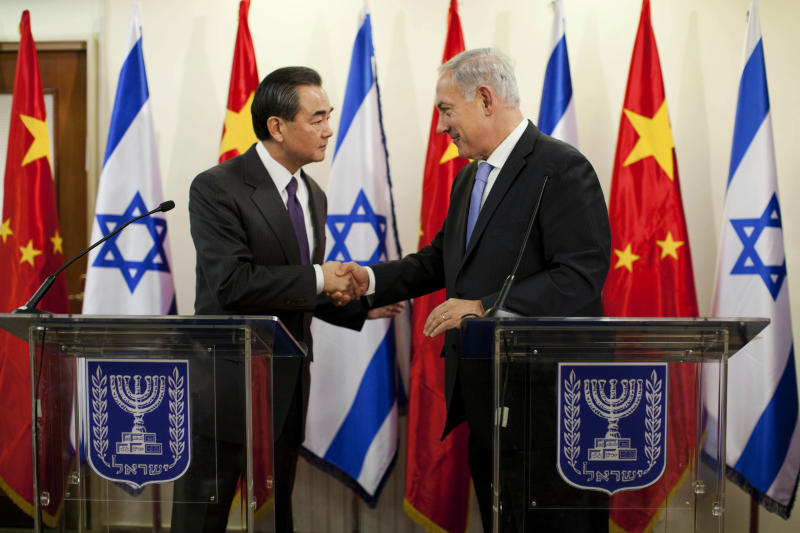 Israeli Prime Minister Benjamin Netanyahu, right, shakes hands with Chinese Foreign Minister Wang Yi before their meeting at the prime minister's office in Jerusalem, Wednesday, Dec. 18, 2013. (AP Photo/Abir Sultan, Pool)