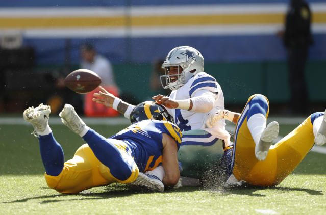 Dallas Cowboys quarterback Dak Prescott (4) is sacked by Los Angeles Rams linebacker Bryce Hager, left, and inside linebacker Natrez Patrick during the first quarter of a preseason NFL football game Saturday, Aug. 17, 2019, in Honolulu. (AP Photo/Marco Garcia)