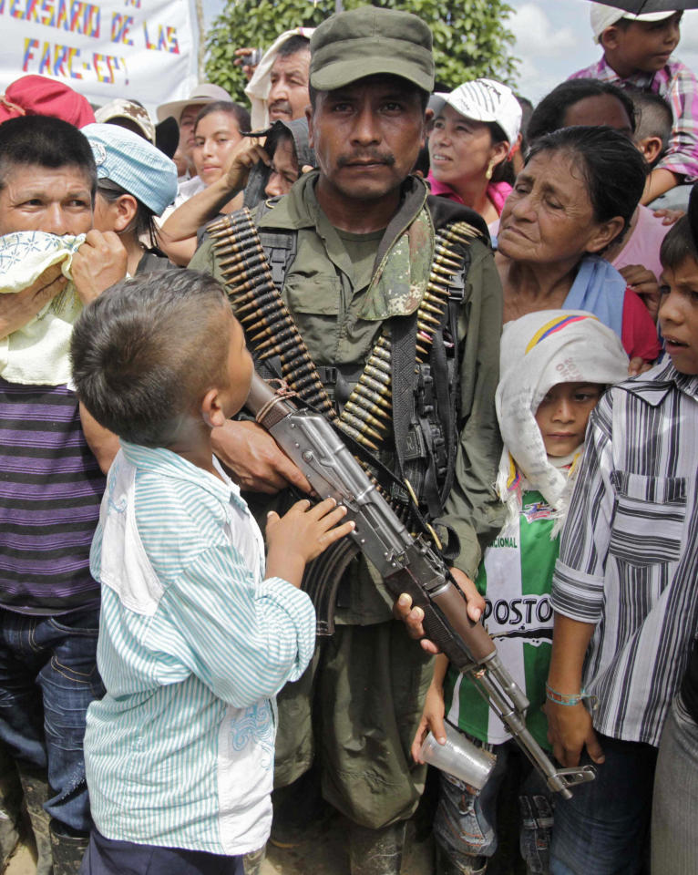 A child looks up at a member of the Revolutionary Armed Forces of Colombia (FARC) during a ceremony for the rebel handover of a French journalist in San Isidro in southern Colombia, Wednesday, May 30, 2012. French journalist Romeo Langlois, who was taken by rebels of the Revolutionary Armed Forces of Colombia (FARC) on April 28 when they attacked troops he was accompanying on a cocaine-lab eradication mission, was handed over by the rebels to a delegation in San Isidro on Wednesday. (AP Photo/Fernando Vergara)