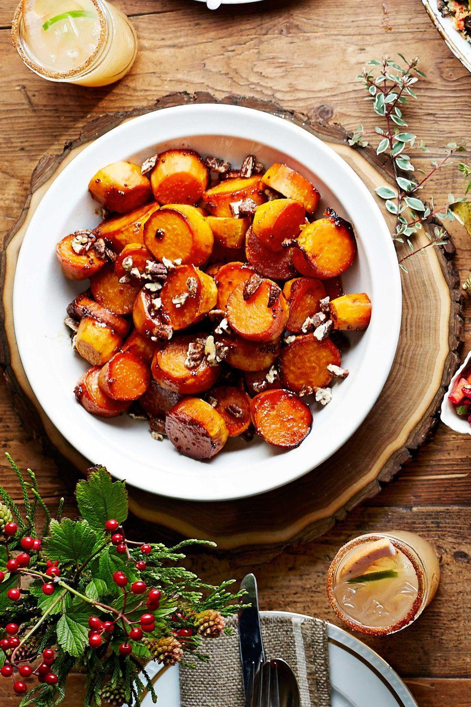 """<p>Store-bought candied or spiced pecans add crunch to this comfort food dish. To make ahead, cover and chill cooked potatoes in glaze in baking dishes the day before. Let stand at room temperature, then reheat covered at 350F for about 20 minutes or until thoroughly heated.</p><p><strong><a href=""""https://www.countryliving.com/food-drinks/recipes/a5913/sorghum-sweet-potatoes-recipe-clx1114/"""" rel=""""nofollow noopener"""" target=""""_blank"""" data-ylk=""""slk:Get the recipe"""" class=""""link rapid-noclick-resp"""">Get the recipe</a>.</strong></p>"""