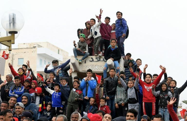 Children chant slogans from atop a sculpture of Mohamed Bouazizi's cart in the square named after him in Sidi Bouzid on Thursday