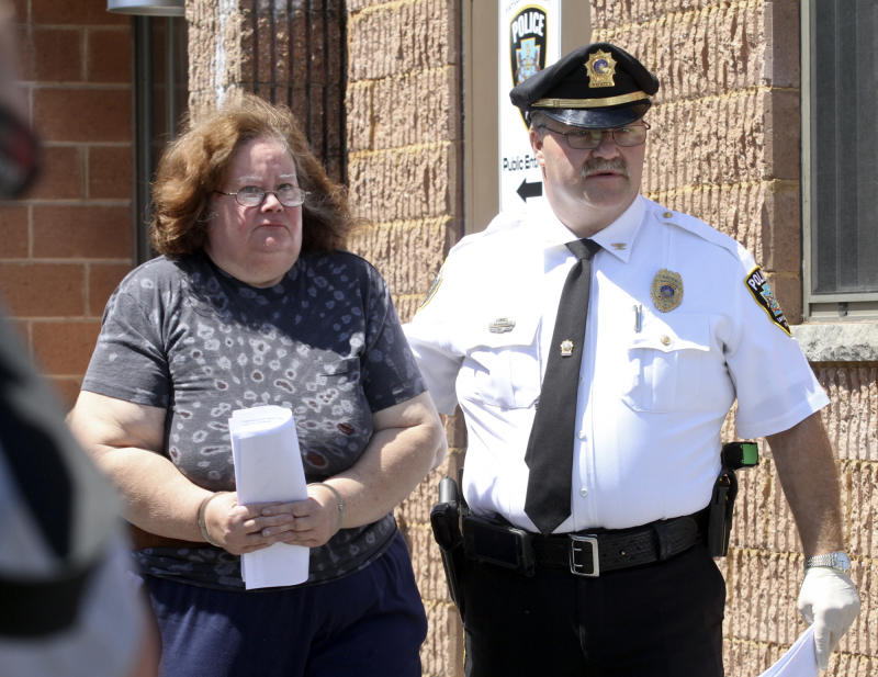 Susan Gensiak, 59, of Taylor, Pa., is lead by a police officer to arraignment, Wednesday, June 19, 2013 in Scranton, Pa. Gensiak and her two daughters have been charged with starving their 32-year-old son and brother, who had Down syndrome, to death. (AP Photo/Scranton Times & Tribune, Michael J. Mullen)  WILKES BARRE TIMES-LEADER OUT; MANDATORY CREDIT