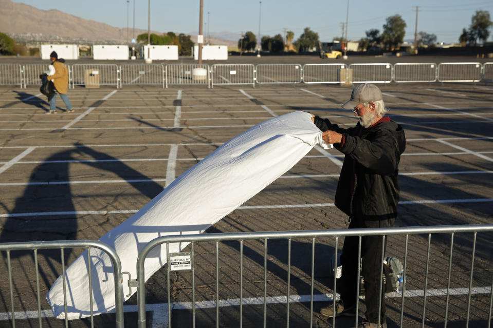 A man prepares a place to sleep on the ground of a parking lot at a makeshift camp for the homeless Monday, March 30, 2020, in Las Vegas. Officials opened part of the lot as a makeshift homeless shelter after a local shelter closed when a man staying there tested positive for the coronavirus. (AP Photo/John Locher)