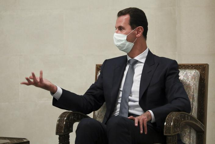In this photo released by Russian Foreign Ministry Press Service, Syrian President Bashar al-Assad gestures while speaking to Russian Foreign Minister Sergey Lavrov during their talks in Damascus, Syria, Monday, Sept. 7, 2020. Russia's foreign minister has met with Syrian President Bashar Assad shortly after landing in the Syrian capital on his first visit since 2012. Russia has been a close ally of Assad in Syria's long and bloody nine-year-long civil war, lending his government in Damascus vital military, economic and political support. (Russian Foreign Ministry Press Service via AP)