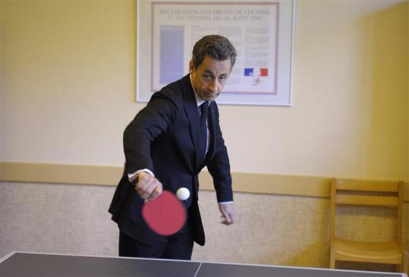 France's President Nicolas Sarkozy plays ping pong as he visits a reintegration school (ERS) in Bagnieres de Luchon, April 14, 2011.