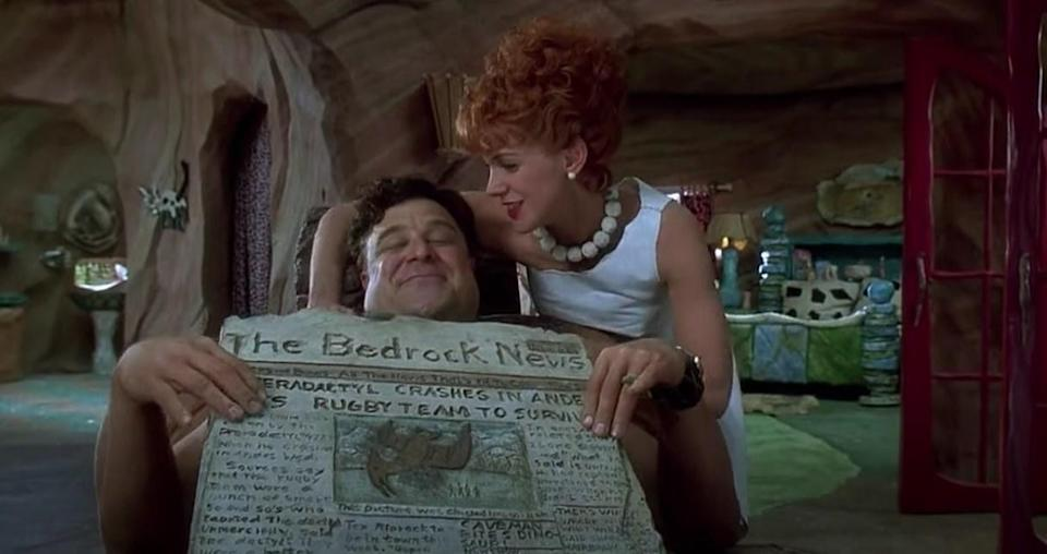 Wilma massages Fred as he reads the newspaper seated in his living room