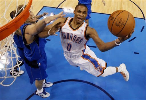 Oklahoma City Thunder guard Russell Westbrook (0) takes the ball to the hoop past Dallas Mavericks Delonte West (13) and Dirk Nowitzki (41) during the first quarter of Game 2 in the first round of the NBA basketball playoffs, in Oklahoma City, Monday, April 30, 2012. Oklahoma City won 102-99. (AP Photo/Nate Billings, Pool)