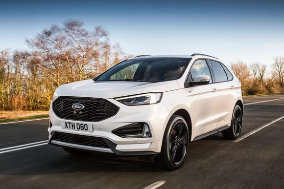 A white 2019 Ford Edge, a midsize SUV, with UK license plate, on a country road.