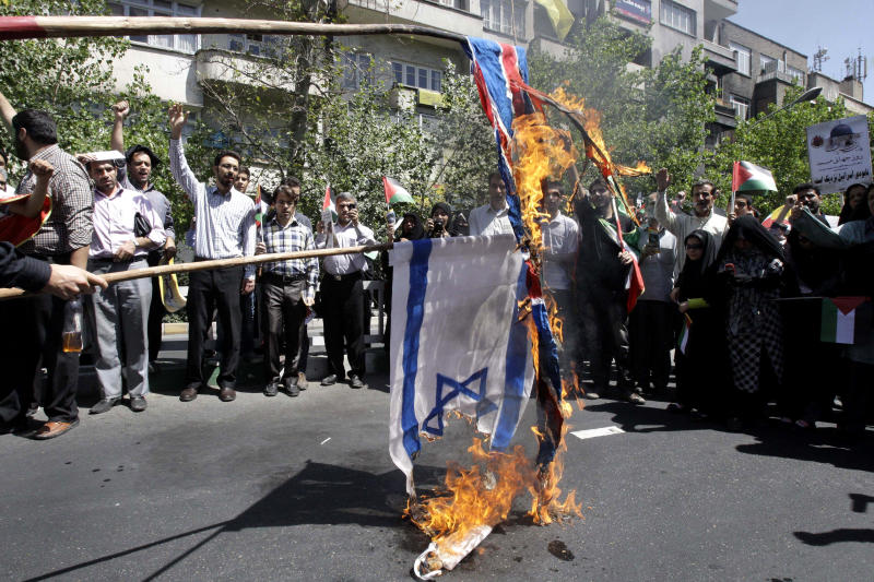 Iranian demonstrators burn an Israeli and British flag during a an annual pro-Palestinian rally marking Quds (Jerusalem) Day, on the last Friday of the holy month of Ramadan, at the Enqelab-e-Eslami (Islamic Revolution) St. in Tehran, Iran, Friday, Aug. 17, 2012. (AP Photo/Vahid Salemi)