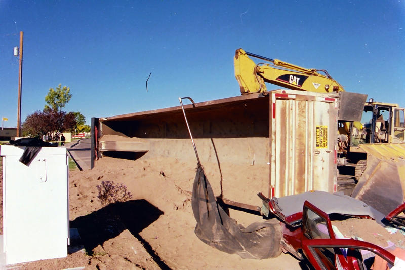 This 2002 photo provided by plaintiff's attorney Vigil Law Firm shows a tractor-trailer that overturned, burying it in sand and suffocating the woman inside, in Albuquergue, N.M. On Monday, Dec. 9, 2013, a judge awarded nearly $80 million to the family of Laura Miera, who suffocated as teachers and students at a nearby school tried to dig her out. District Judge Shannon Bacon entered the judgment to the 48-year-old woman's husband and daughter, including $60 million of punitive damages, against Albuquerque Redi-Mix and another company and owners of both companies, John and Barbara Quintana. (AP Photo/Courtesy Vigil Law Firm)