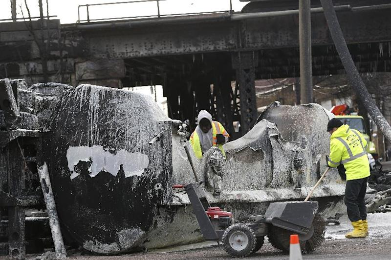 Crews clean up the site where a tanker overturned and burst into flames early in the morning near train tracks on Route 21 in Newark, N.J., Thursday, March 13, 2014. The tanker burst into flames after colliding with a car on McCarter Highway adjacent to Amtrak's Northeast Corridor rail line in Newark at about 1:45 a.m. Thursday. That caused problems for Amtrak's signals and overhead wires. Amtrak service is running with minor delays. (AP Photo/Julio Cortez)