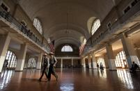 FILE - National Park Service rangers walk through the Great Hall at Ellis Island, on April 29, 2015, in New York. The location is featured in a collection of mini-essays by American writers published online by the Frommer's guidebook company about places they believe helped shape and define America. (AP Photo/Julie Jacobson, File)