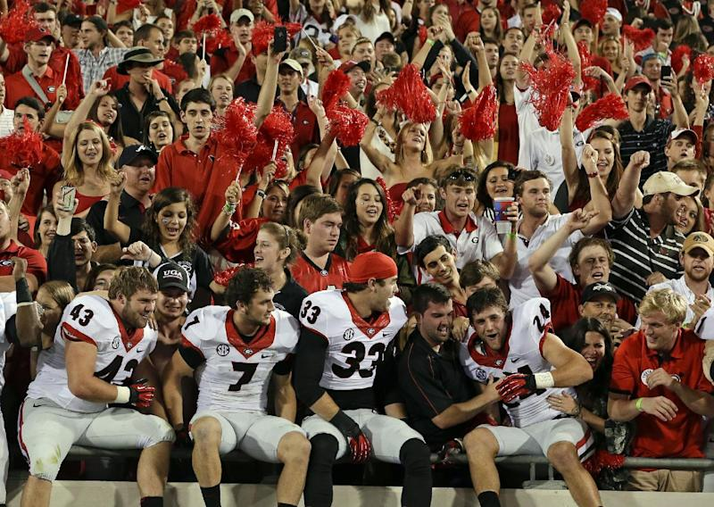 Georgia players Merritt Hall (43), Blake Sailors (7), Chase Vasser (33), and Lucas Redd (24) celebrate with fans after their 23-20 win over Florida in an NCAA football game, Saturday, Nov. 2, 2013, in Jacksonville, Fla