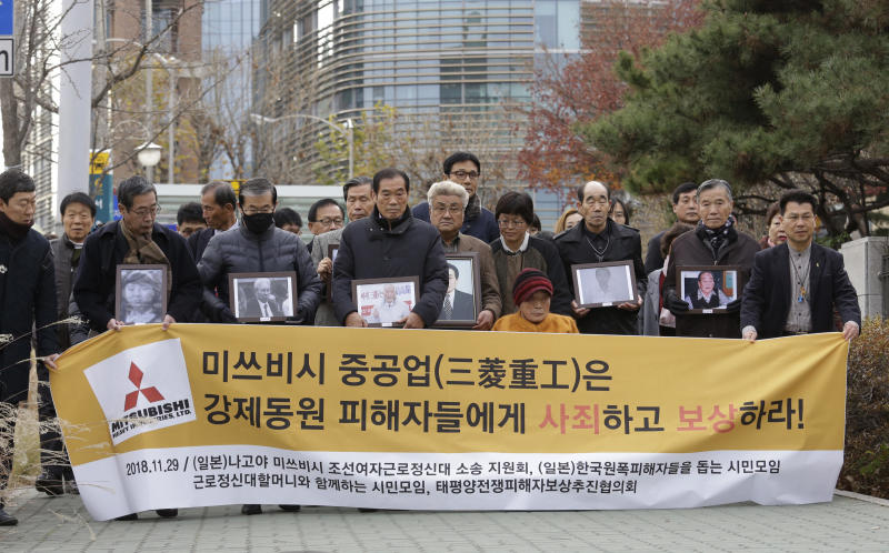 """FILE - In this Nov. 29, 2018, file photo, victims of Japan's forced labor and their family members arrive at the Supreme Court in Seoul, South Korea. Colonial-era Korean laborers on Tuesday, July 16, 2019, are seeking a court's approval for the sales of local assets of their former Japanese employer after it refused to comply with a court order to compensate them for forced labor decades ago. The sign reads """"Mitsubishi Heavy Industries should compensate and apologize to victims of forced labor."""" (AP Photo/Ahn Young-joon, File)"""