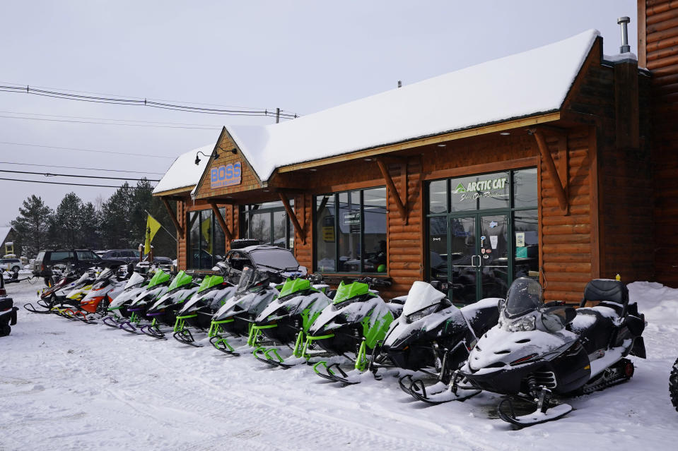 Snowmobiles are lined up outside a shop, Saturday, Jan. 23, 2021, in Rangeley, Maine. This year the market is red hot for snowmobiles, just like the market for boats, bicycles and ATVs — anything that keeps people occupied, outdoors and safe during a pandemic that has pushed families indoors. (AP Photo/Robert F. Bukaty)