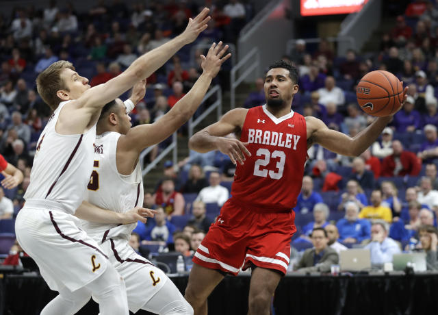 Bradley's Dwayne Lautier-Ogunleye (23) passes around Loyola of Chicago's Bruno Skokna, left, and Marques Townes during the second half of an NCAA college basketball game in the semifinal round of the Missouri Valley Conference tournament, Saturday, March 9, 2019, in St. Louis. Bradley won 53-51. (AP Photo/Jeff Roberson)