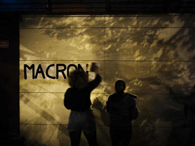 "In this Oct. 24 2019, photo, Maya, 19, a student from Versailles pastes a slogan with the name of French President Emmanuel Macron in the evening in the south of Paris. France, a country that has prided itself on gender equality, is beginning to pay serious attention to its yet-intractable problem of domestic violence. Under cover of night, activists have glued slogans to the walls to draw attention to domestic violence, a problem French President Emmanuel Macron has called ""France's shame."" (AP Photo/Kamil Zihnioglu)"