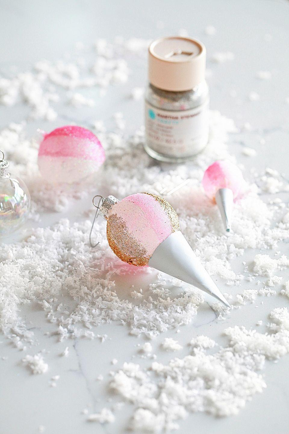 """<p>To make a super sweet DIY ornament, fashion a cone out of silver scrapbook paper, then glue it onto a glitter-covered ornament. </p><p><em>Get the tutorial at <a href=""""https://poshlittledesigns.com/2017/12/21/snow-cone-ornaments-diy/"""" rel=""""nofollow noopener"""" target=""""_blank"""" data-ylk=""""slk:Posh Little Designs"""" class=""""link rapid-noclick-resp"""">Posh Little Designs</a>. </em></p><p><a class=""""link rapid-noclick-resp"""" href=""""https://www.amazon.com/Hygloss-Products-Metallic-Board-Sheets/dp/B01MEDJR1E/?tag=syn-yahoo-20&ascsubtag=%5Bartid%7C10072.g.34443405%5Bsrc%7Cyahoo-us"""" rel=""""nofollow noopener"""" target=""""_blank"""" data-ylk=""""slk:SHOP SILVER PAPER"""">SHOP SILVER PAPER</a></p>"""