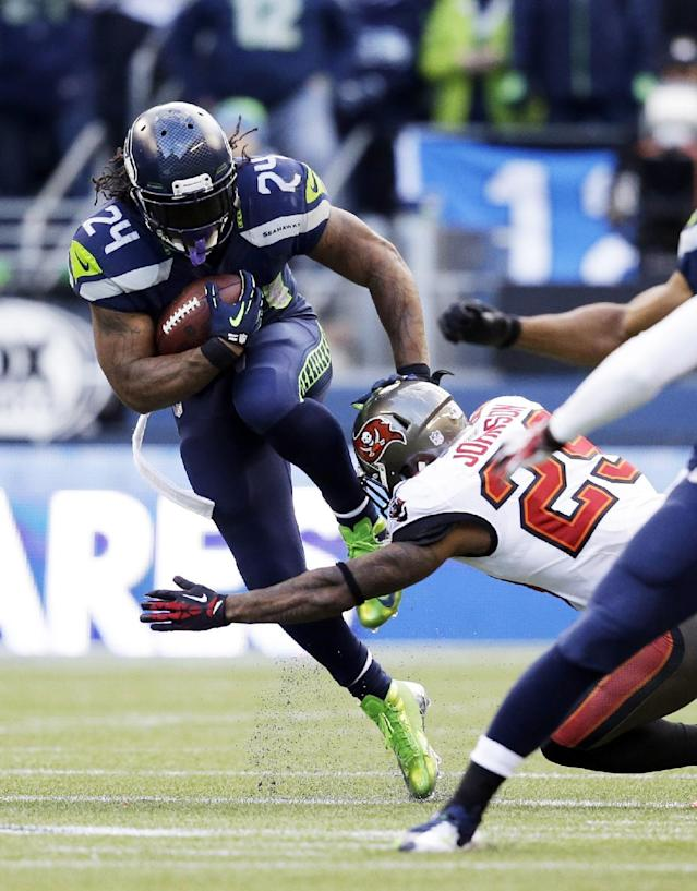 Seattle Seahawks' Marshawn Lynch leaps to try and avoid a tackle from cornerback Leonard Johnson in the second half of an NFL football game Sunday, Nov. 3, 2013, in Seattle. The Seahawks won 27-24 in overtime. (AP Photo/Elaine Thompson)