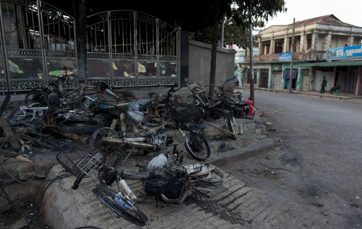 Army officers stand guard outside a burned mosque in Lashio, northern Shan State, Myanmar, Wednesday, May 29, 2013. Hundreds of Buddhist men on motorcycles waved iron rods and bamboo poles and threw rocks in a northeastern Myanmar town on Wednesday, a day after a mosque and a Muslim orphanage were torched in a new wave of violence targeting the religious minority.(AP Photo/Gemunu Amarasinghe)