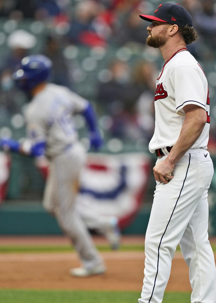 Cleveland Indians starting pitcher Logan Allen, right, waits for Kansas City Royals Whit Merrifield to run the bases after Merrifield hit a two-run home run in the second inning of a baseball game, Monday, April 5, 2021, in Cleveland. (AP Photo/Tony Dejak)