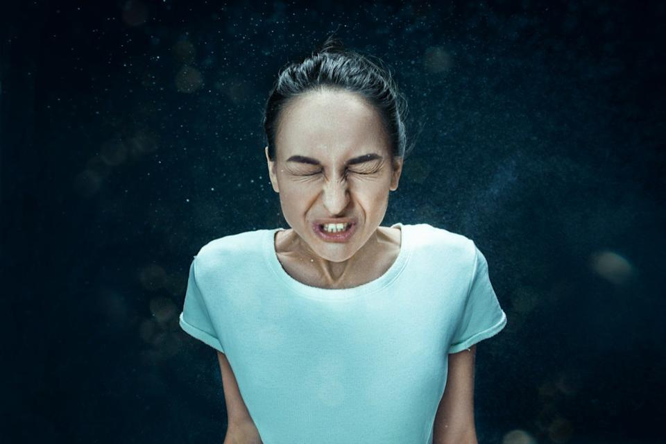woman sneezing with spray and small drops