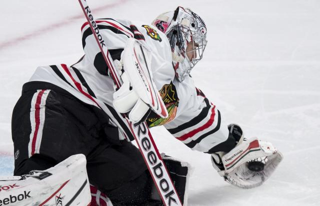 Chicago Blackhawks goalie Corey Crawford gloves the puck during the first period of an NHL hockey game against the Montreal Canadiens, Saturday, Jan. 11, 2014, in Montreal. (AP Photo/The Canadian Press, Paul Chiasson)