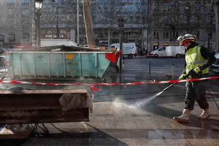 """A construction worker cleans the pavement on the Champs Elysees Avenue on the eve of demonstrations by """"yellow vests"""" protesters in Paris, France, December 14, 2018. REUTERS/Benoit Tessier"""