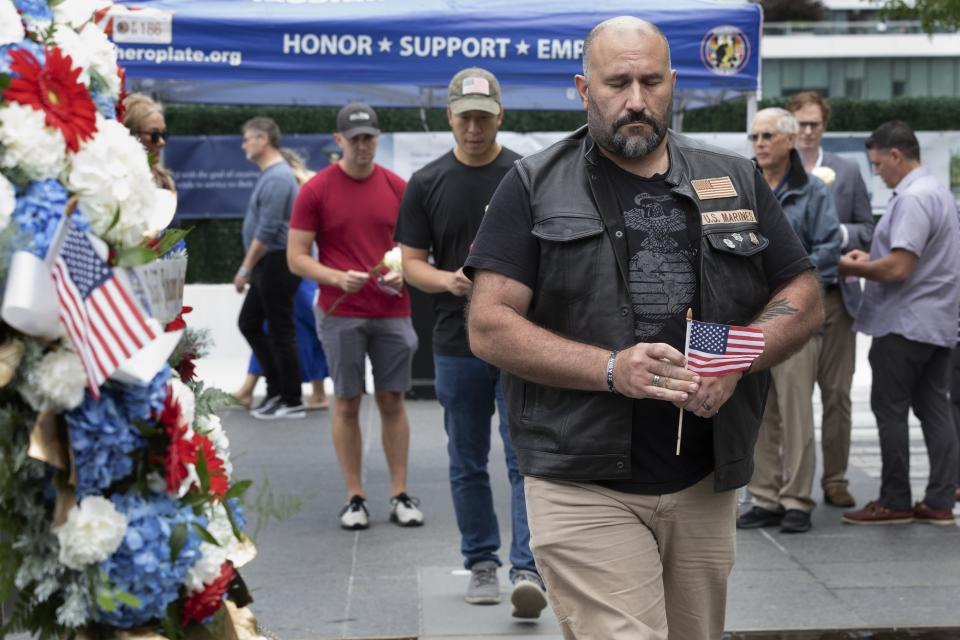 Brian Abelli, foreground, walks past a wreath in memory of Marine Sgt. Johanny Rosario Pichardo from Lawrence, Mass., after placing a rose at the Massachusetts Fallen Heroes Memorial, Saturday, Aug. 28, 2021, in Boston. The ceremony was held to honor the U.S. service members killed in a suicide bombing at the airport in Kabul, Afghanistan, including Sgt. Rosario Pichardo. (AP Photo/Michael Dwyer)