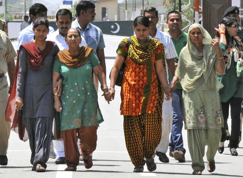 Sarabjit Singh's wife Sukhpreet Kaur, right, sister Dalbir Kaur, second from left, and daughters Poonam, left, and Swapandeep hold hands and walk after entering Indian soil at the India-Pakistan border area of Wagah, India, Wednesday, May 1, 2013. The family members traveled to Pakistan Sunday to meet Singh, an Indian spy on death row in Pakistan, who was critically injured Friday when he was attacked with a brick by two other prisoners inside a prison in the eastern city of Lahore. (AP Photo/Prabhjot Gill)