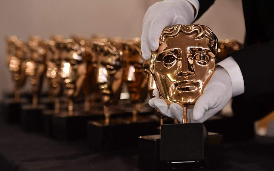 A member of staff polishes BAFTA awards - AFP or licensors