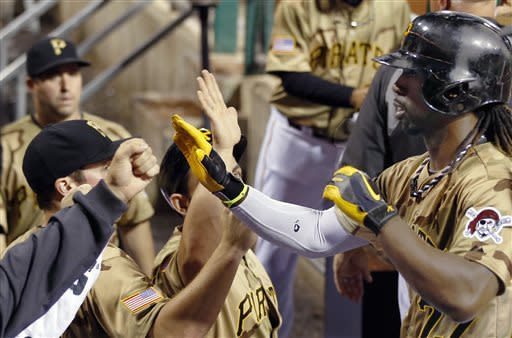 Pittsburgh Pirates' Andrew McCutchen, right, is greeted by teammates in the dugout after scoring on a single by Brandon Inge in the sixth inning of the baseball game against the Houston Astros, Saturday, May 18, 2013, in Pittsburgh. (AP Photo/Keith Srakocic)