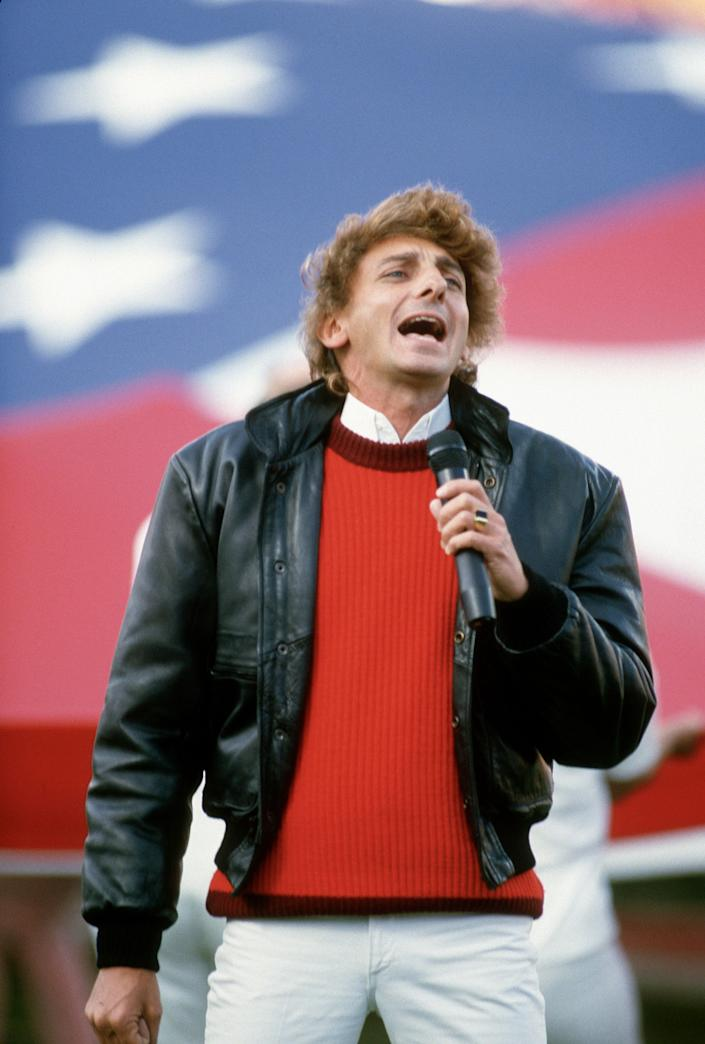 Barry Manilow sings the National Anthem prior to Super Bowl XVIII between the Washington Redskins and Los Angeles Raiders on January 22, 1984 at Tampa Stadium in Tampa, Florida. The Raiders won the Super Bowl 38 - 9.