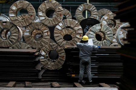 FILE PHOTO - A worker checks steel coils and steel sheets at a distribution warehouse in Urayasu, east of Tokyo