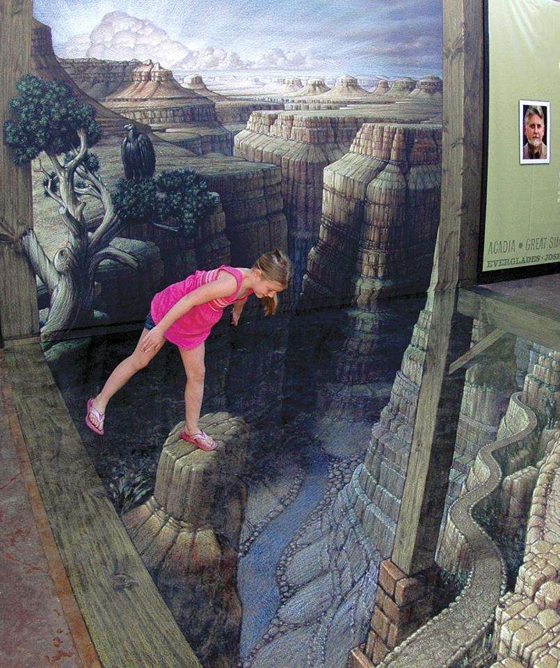 "This June 15, 2012 photo released by the National Geographic Visitor Center at Grand Canyon shows an unidentified visitor examining the sidewalk artwork ""Grand Canyon Illusion"" by artist Kurt Wenner outside the National Geographic Visitor Center at the South Rim of the Grand Canyon near Tusayan, Ariz., in this handout photo made on June 15, 2012. The 3-D piece gives the illusion of being perched atop spires and starting down a winding trail that seemingly plunges into the depths of the massive gorge. (AP Photo/National Geographic Visitor Center at Grand Canyon, Joel Kramer)"