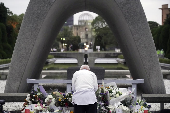 A man prays in front of the cenotaph for the atomic bombing victims before the start of ceremony to mark the 75th anniversary of the bombing in Hiroshima, western Japan, early Thursday, Aug. 6, 2020. (AP Photo/Eugene Hoshiko)